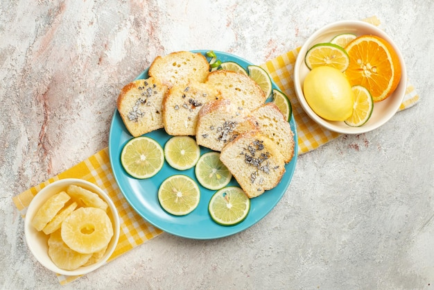 Bovenaanzicht plaat op het tafelkleed blauwe plaat van cake en limoen naast de kommen met gedroogde ananas en citrusvruchten op het geruite tafelkleed