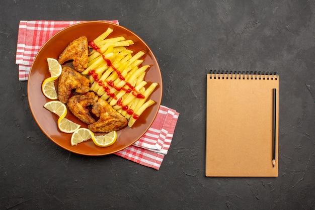 Bovenaanzicht plaat op tafelkleed oranje plaat van smakelijke frietjes kippenvleugels ketchup en citroen op roze-wit geruit tafelkleed naast het crèmekleurige notitieboekje en zwart potlood