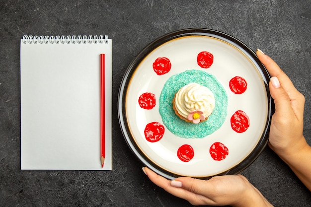 Bovenaanzicht plaat van cupcake wit notitieboekje en rood potlood naast de cupcake op de witte plaat in handen op de donkere achtergrond