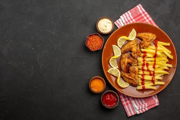 Bovenaanzicht plaat van fastfood kippenvleugels frietjes met citroen en ketchup en kommen met sauzen en kruiden op roze-wit geruit tafelkleed aan de rechterkant van zwarte tafel