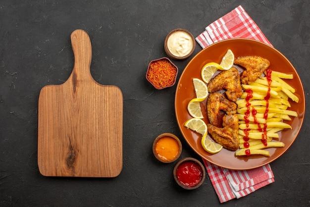 Bovenaanzicht plaat van fastfood kippenvleugels frietjes met citroen en ketchup en kommen met sauzen en kruiden op roze-wit geruit tafelkleed naast de houten snijplank