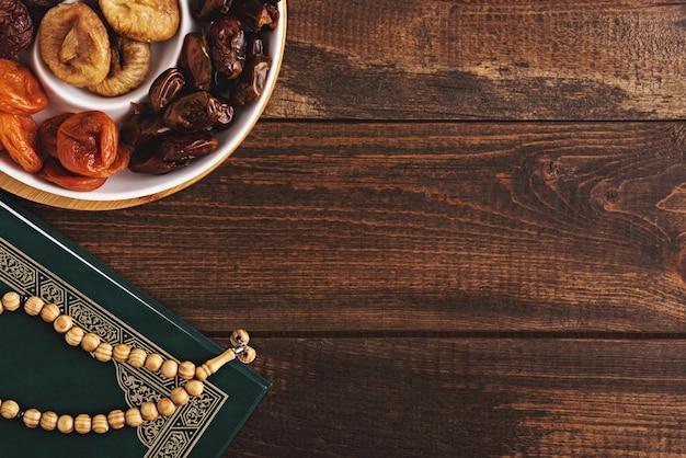 Bovenaanzicht plaat van gedroogd fruit, houten rozenkrans, koran op bruin houten achtergrond, iftar concept, ramadan, islamitische vakantie, kopie ruimte