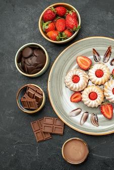 Bovenaanzicht plaat van koekjes plaat van aardbeienkoekjes met chocolade en kommen chocolade aardbei en chocoladeroom op donkere ondergrond