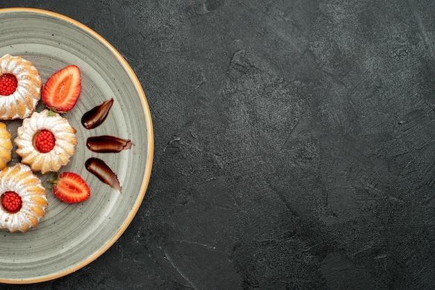 Bovenaanzicht plaat van koekjes plaat van smakelijke koekjes met chocolade en aardbei aan de linkerkant van de tafel