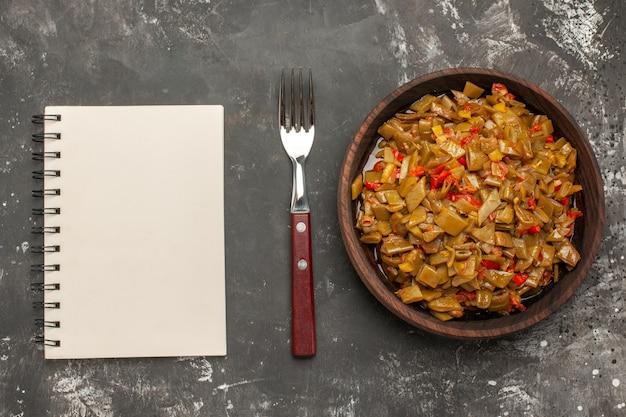 Bovenaanzicht plaat van sperziebonen bruine plaat van de smakelijke sperziebonen en tomaten naast het witte notitieboekje en de vork op de donkere tafel
