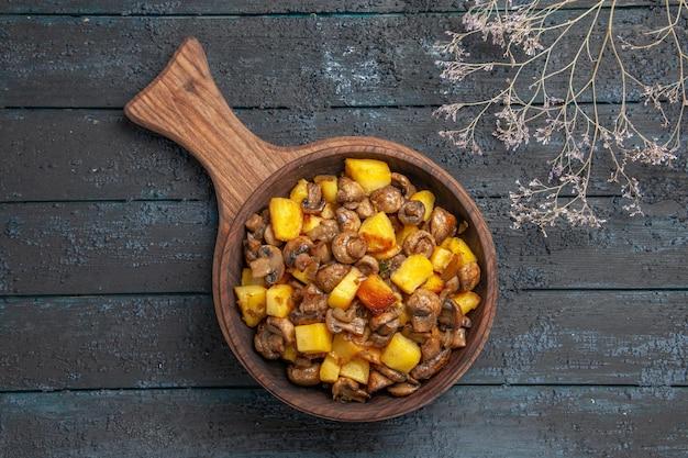 Bovenaanzicht plaat van warme schotel bruine plaat van aardappelen en champignons op de snijplank op de donkere achtergrond naast de boomtakken