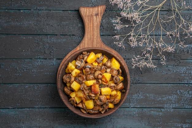 Bovenaanzicht plaat van warme schotel plaat van gebakken aardappelen en champignons op de snijplank op het donkere oppervlak naast de takken