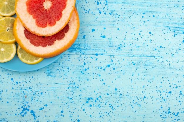 Bovenaanzicht plakjes fruit grapefruit en schijfjes citroen op de helderblauwe vloer