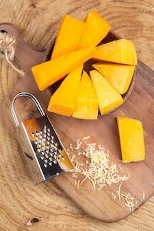 Bovenaanzicht plakjes kaas in houten kom doos rasp op snijplank op houten tafel