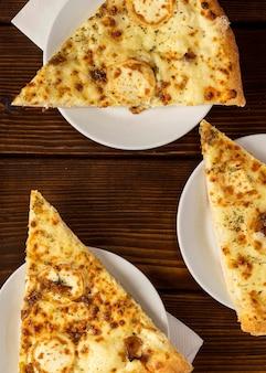 Bovenaanzicht plakjes pizza met kaas op plaat