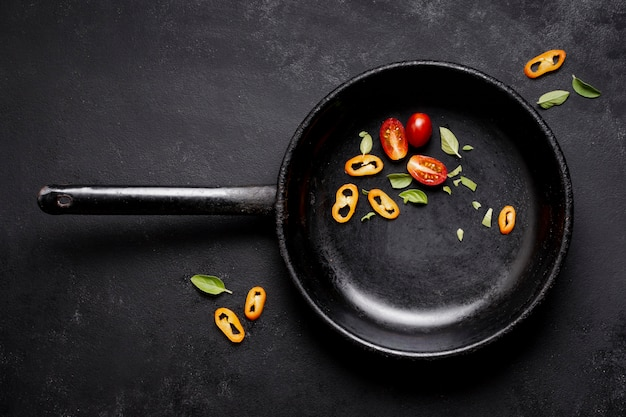 Bovenaanzicht plakjes tomaten en chili peper in de pan