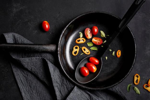 Bovenaanzicht plakjes tomaten en chili peper in een koekenpan