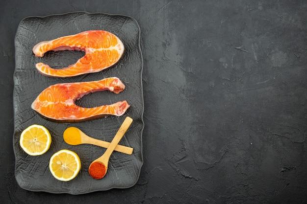 Bovenaanzicht plakjes vers vlees in plaat met schijfjes citroen op donkere achtergrond