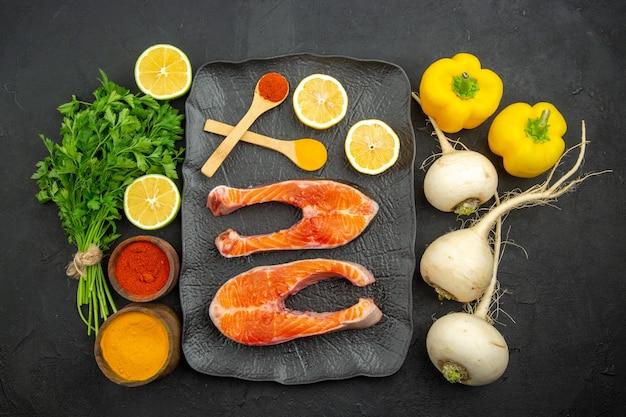 Bovenaanzicht plakjes vers vlees met groene citroen en kruiden op donkere achtergrond