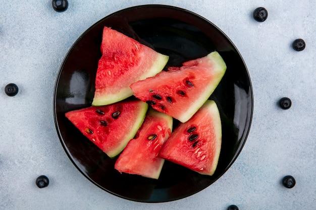 Bovenaanzicht plakjes watermeloen op een bord met bosbessen