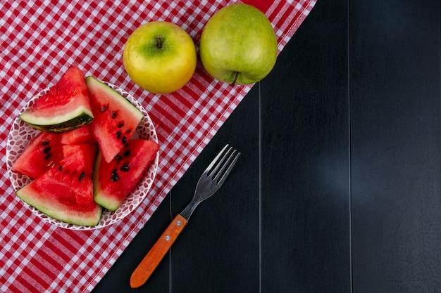 Bovenaanzicht plakjes watermeloen op een rode keuken handdoek met appels en een vork op een zwarte achtergrond