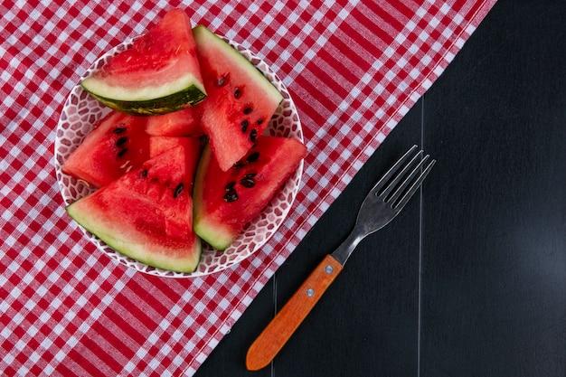 Bovenaanzicht plakjes watermeloen op een rode keuken handdoek met een vork op een zwarte achtergrond