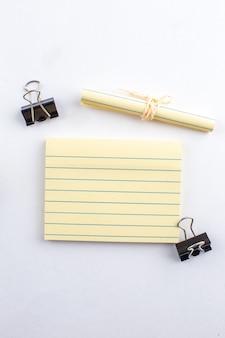 Bovenaanzicht plaknotitie bindmiddel clips opgerold papier vastgebonden met touw op witte tafel