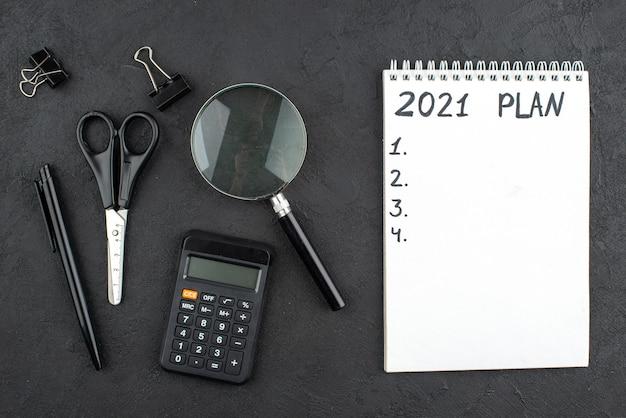 Bovenaanzicht plan doelenlijst geschreven op notitieblok rekenmachine schaar lupa bindmiddel clips pen op donkere muur