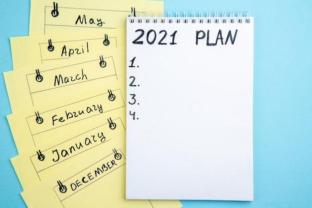 Bovenaanzicht plan geschreven op papier op spiraalvormige notitieboekje maandelijkse herinneringskaarten op blauwe tafel