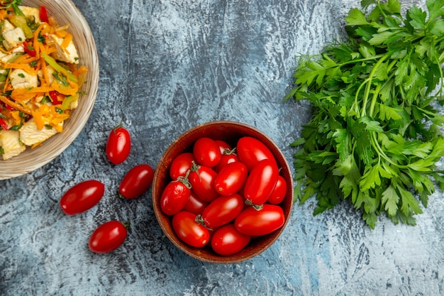 Bovenaanzicht plantaardige kipsalade met rode tomaten op licht bureau