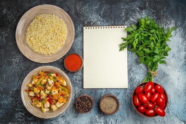 Bovenaanzicht plantaardige kipsalade met tomaten en greens op licht bureau