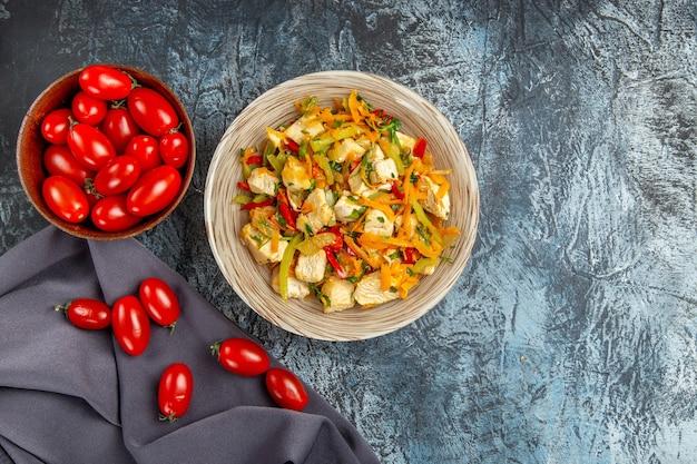 Bovenaanzicht plantaardige kipsalade met tomaten op het lichtbureau