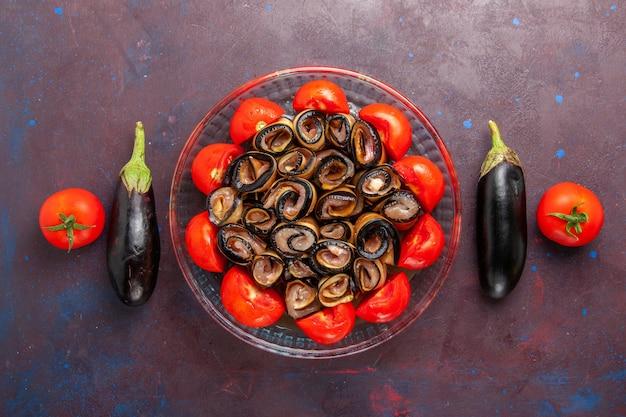 Bovenaanzicht plantaardige maaltijd gesneden en gerolde tomaten met aubergines op de donkere achtergrond