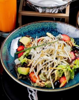 Bovenaanzicht plantaardige salade met fruit, aardbeien en druiven in een plaat