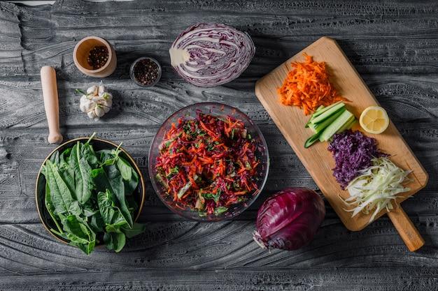 Bovenaanzicht plantaardige salade met gesneden groenten, groenen en kruiden op donkere houten achtergrond. horizontaal