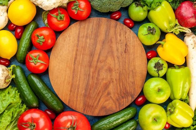 Bovenaanzicht plantaardige samenstelling met vers fruit op blauwe tafel maaltijdsalade gezond leven rijp kleurendieet