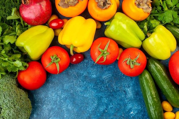 Bovenaanzicht plantaardige samenstelling met vers fruit op blauwe tafel