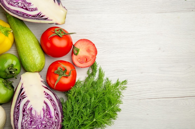 Bovenaanzicht plantaardige samenstelling tomaten kool paprika met groenen op witte achtergrond