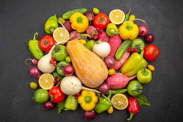 Bovenaanzicht plantaardige samenstelling verse groenten met pompoen op een donkere achtergrond