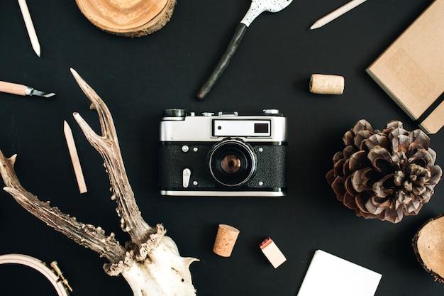 Bovenaanzicht, plat lag hipster fotograaf concept. retro camera, geitenhoorns, handgemaakte lepel, ambachtelijk dagboek, kegel op zwart krijtbord.