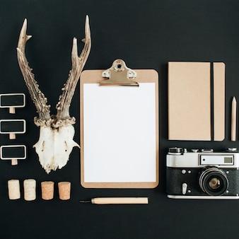 Bovenaanzicht, plat lag hipster fotograaf concept. retro camera, geitenhoorns, klembord, ambachtdagboek op zwart krijtbord.