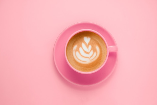 Bovenaanzicht plat lag koffie met latte art roze kop op een zacht pastelroze
