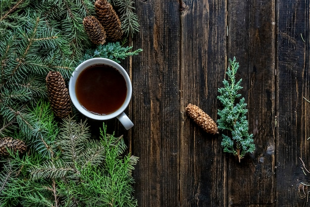 Bovenaanzicht plat lag kopje thee in de buurt van pijnboomtakken op een houten oppervlak.