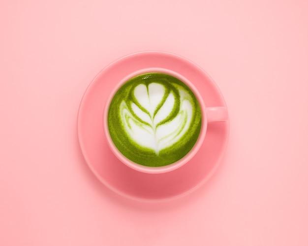 Bovenaanzicht plat lag matcha groene theekop op een pastelroze