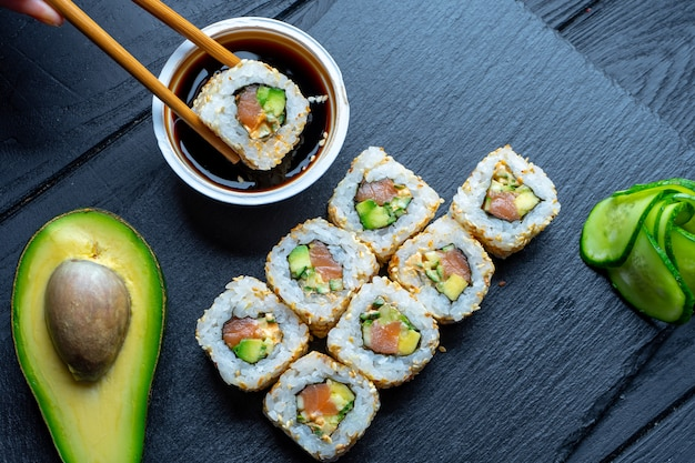 Bovenaanzicht plat lag sushi roll op donkere stenen plaat op donkere achtergrond met kopie ruimte. rol met avocado en zalm. zeevruchten. doop sushi in sojasaus. concept van de aziatische keuken