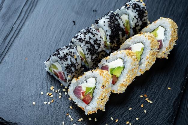 Bovenaanzicht plat lag sushi roll op donkere stenen plaat op donkere muur met kopie ruimte. rol met tonijn en roomkaas. zeevruchten. doop sushi in sojasaus. concept van de aziatische keuken