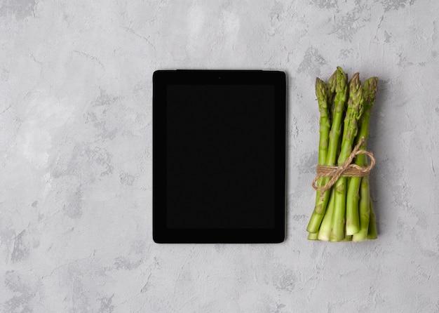 Bovenaanzicht plat lag van verse groene asperges met tablet op grijze betonnen tafel