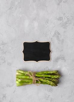 Bovenaanzicht plat lag van verse groene asperges op grijze betonnen tafel