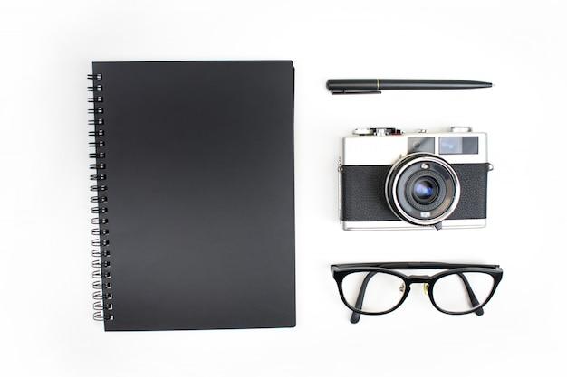 Bovenaanzicht, plat lag, zwart thema van notebooks, filmdozen, leesbril en pennen geïsoleerd