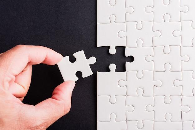 Bovenaanzicht plat leggen van de hand met het laatste stukje puzzelspel