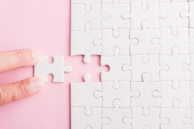 Bovenaanzicht plat leggen van handhoudend laatste stuk wit papier puzzelgame laatste stukjes op hun plaats voor het oplossen van een complete missie