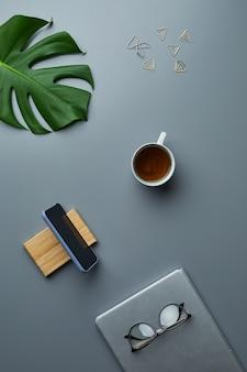 Bovenaanzicht plat leggen van tropisch blad en zakelijke accessoires over grijze werkplek achtergrond,