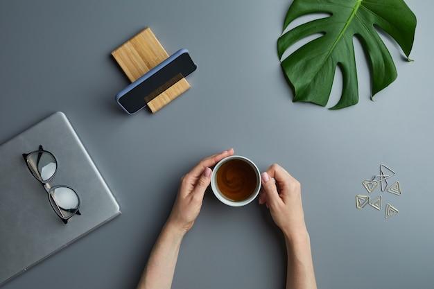 Bovenaanzicht plat leggen van vrouwelijke handen met koffiekopje over grijze werkplek achtergrond met zakelijke gadgets en tropisch blad,