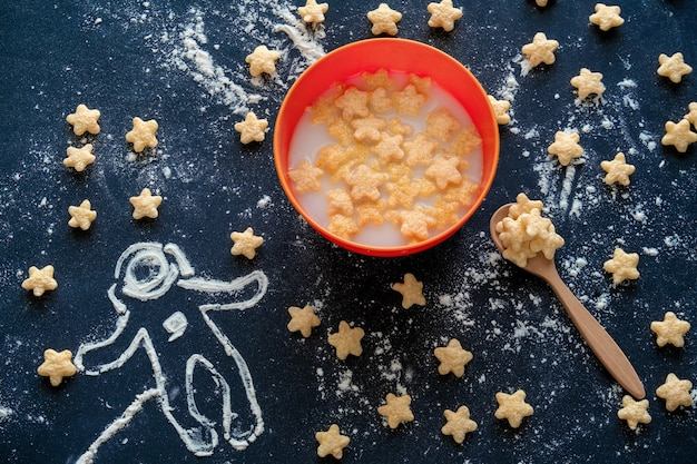 Bovenaanzicht platte kom melk met maïs pads in de vorm van sterren