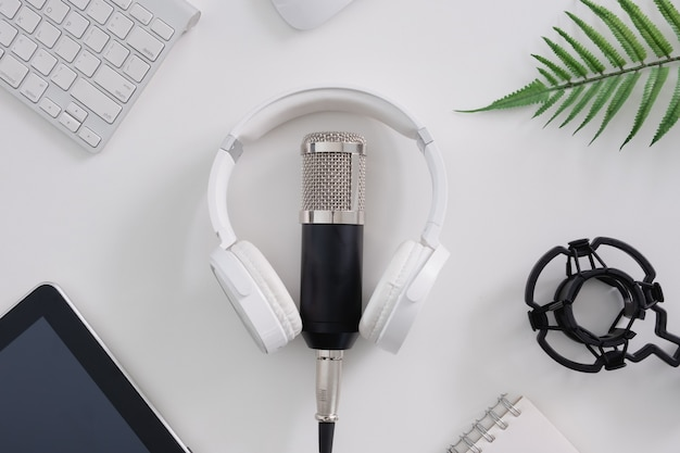Bovenaanzicht podcast microfoon, toetsenbord, tablet en koptelefoon op witte achtergrond